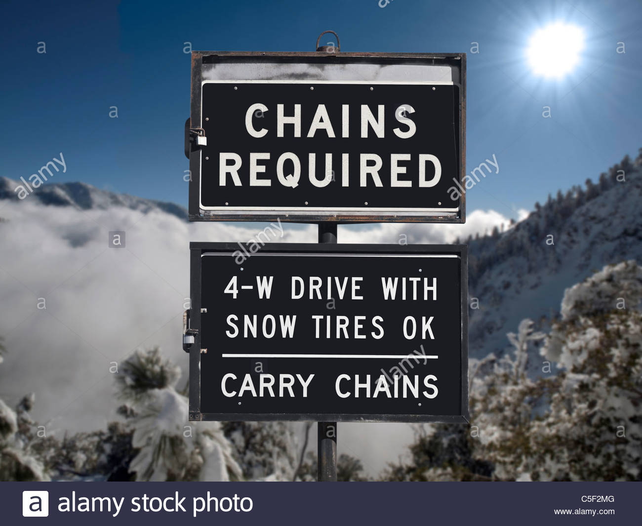 Chains or snow tires required sign with mountain backdrop. - Stock Image