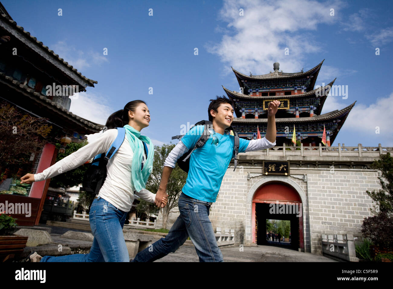 Young Couple Running Through Dali - Stock Image