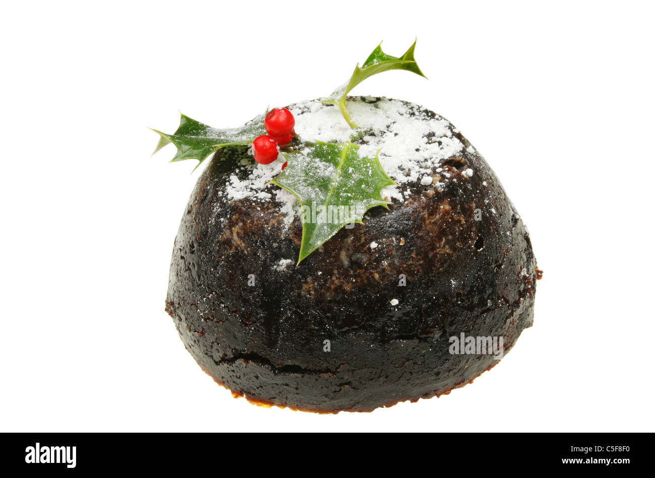 Christmas pudding dusted with sugar and decorated with a holly sprig - Stock Image