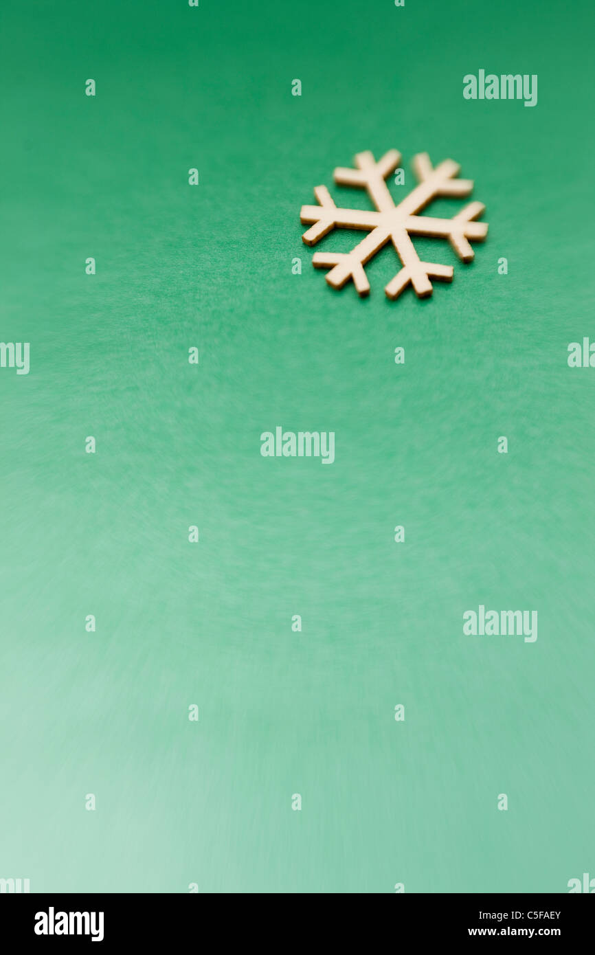 Snowflake ornament on green background - Stock Image