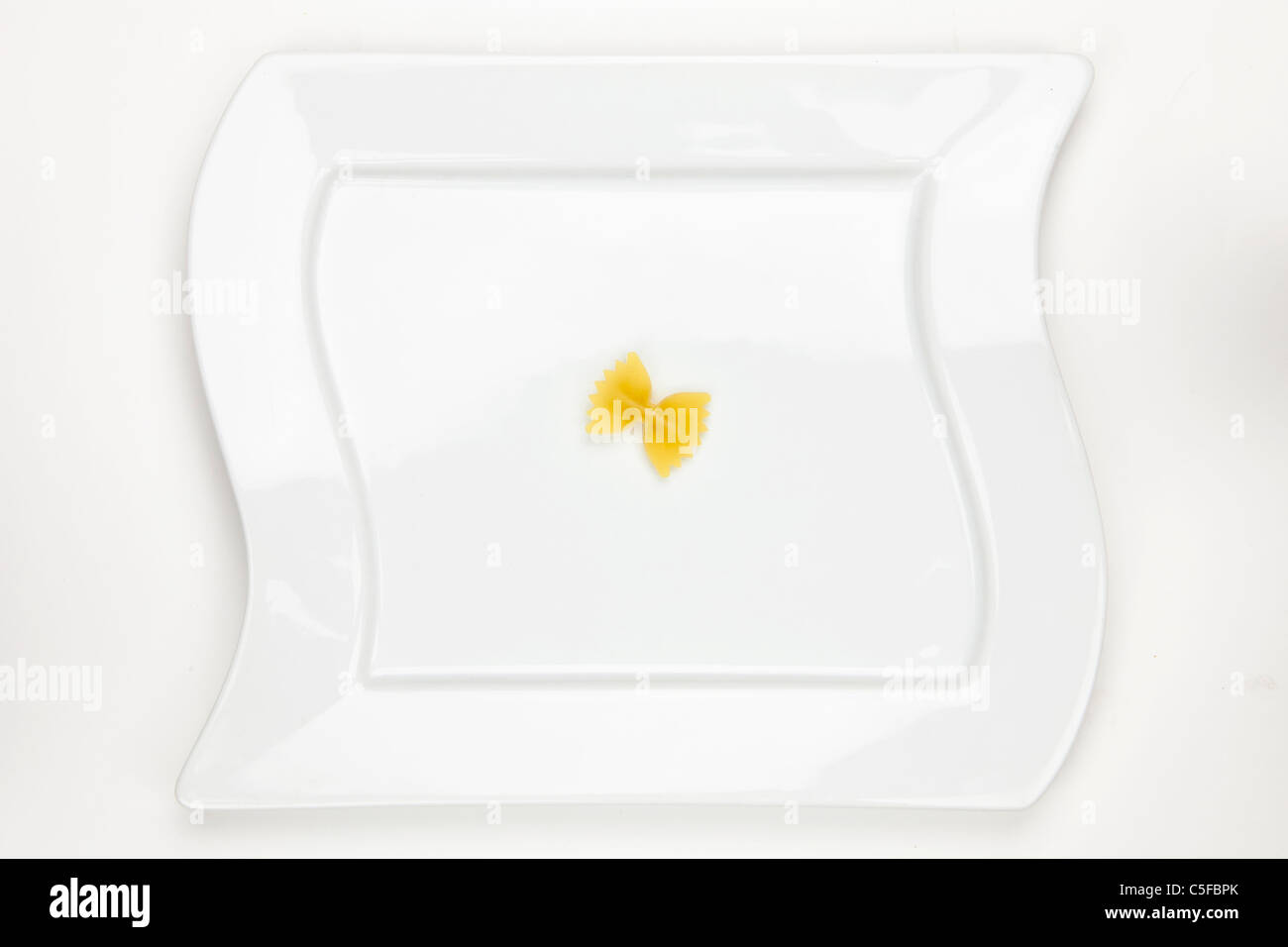 Farfalle one on a white plate - Stock Image