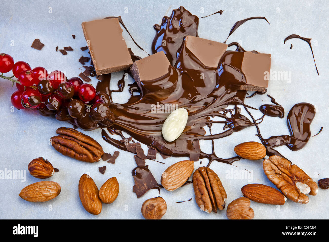 smooth chocolate pieces with chocolate sauce and nuts, and red currants - Stock Image