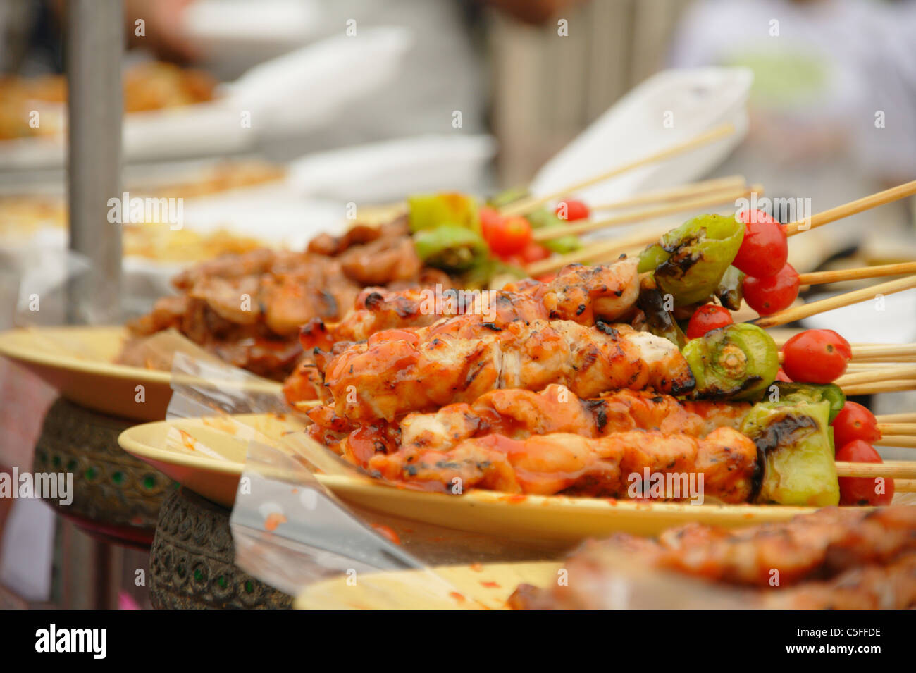 Thai cuisine barbecue chicken and pork skewers at Chatuchak weekend market in Bangkok, Thailand - Stock Image