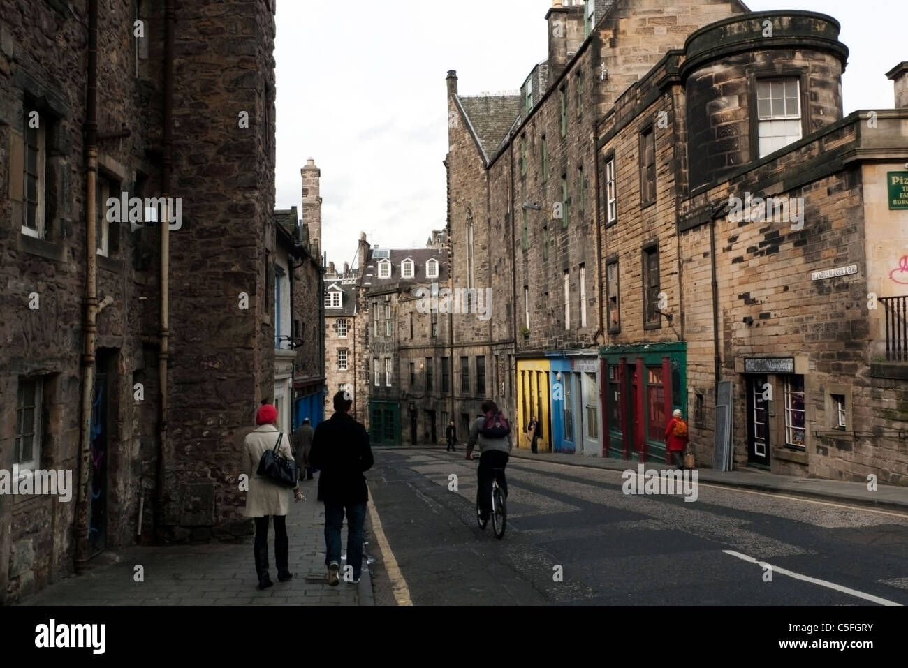 People strolling and cycling along Candlemaker Row In Edinburgh Scotland UK Stock Photo