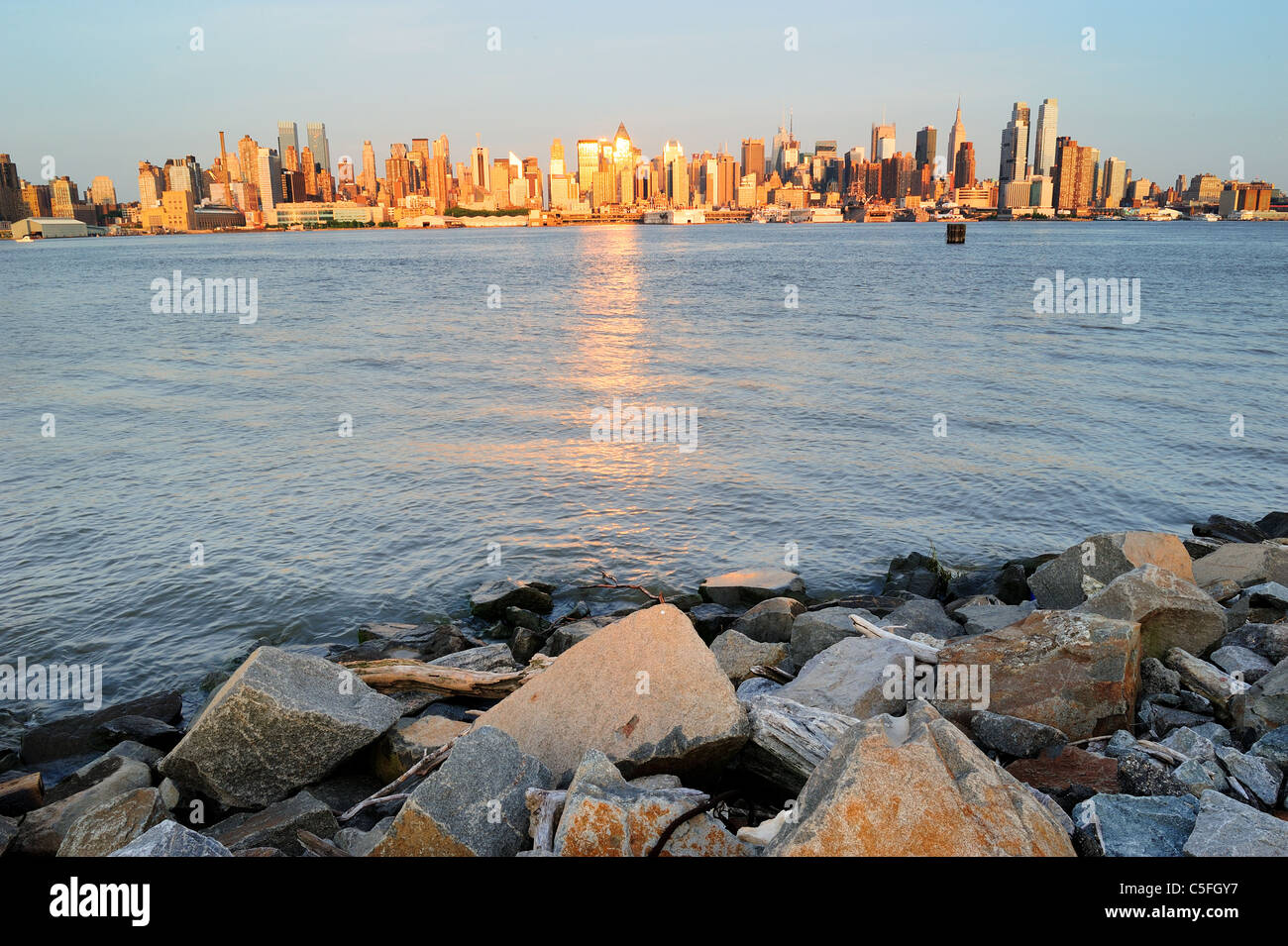 New York City Manhattan midtown skyline at sunset with reflection over skyscraper and river viewed from New Jersey Stock Photo