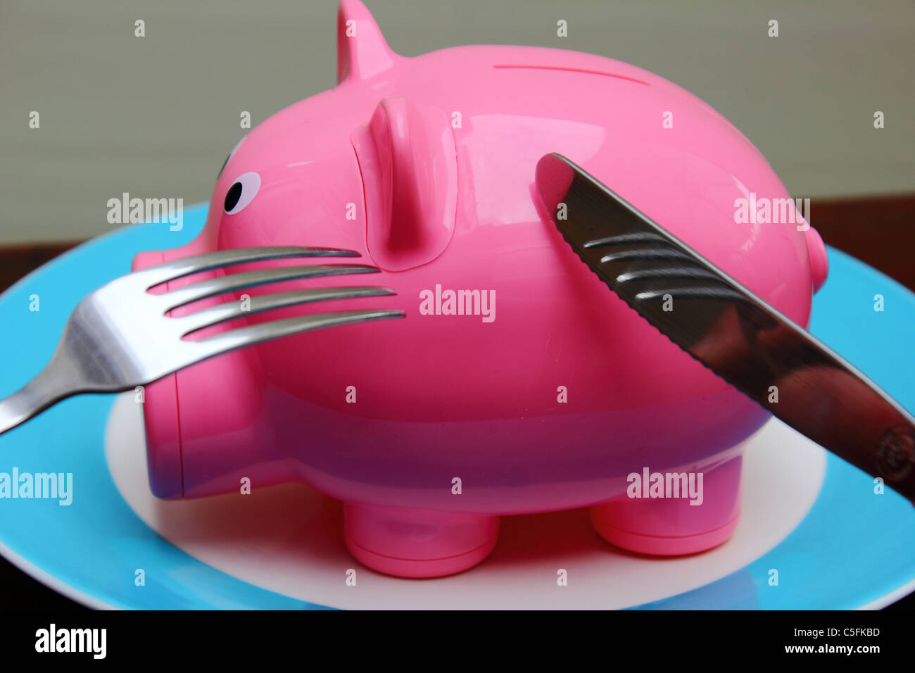 a piggy bank on a plate ready to been eaten, conceptual image - Stock Image