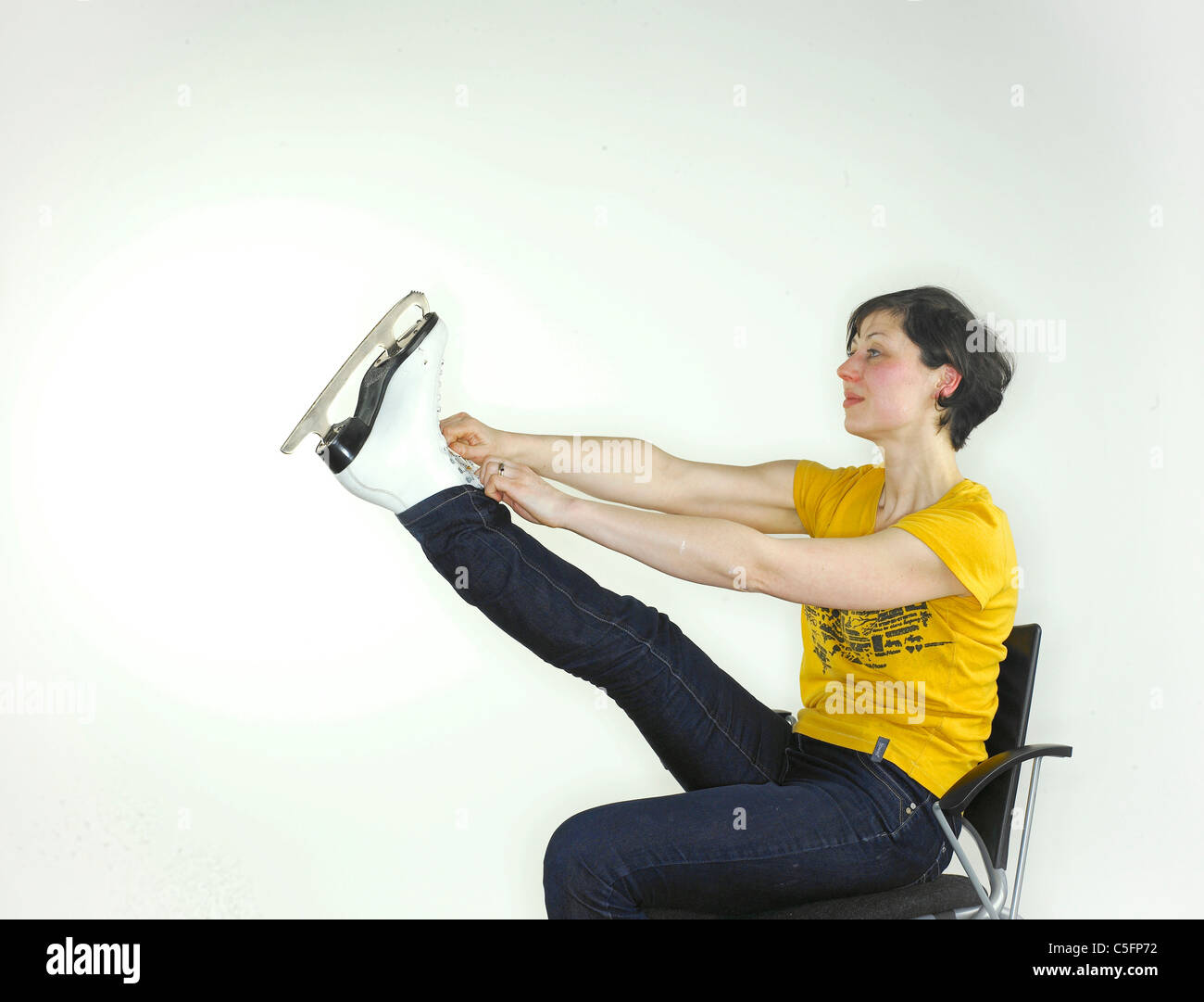 A young caucasian woman putting on an ice skate, holding her leg up high  to tie the laces. - Stock Image