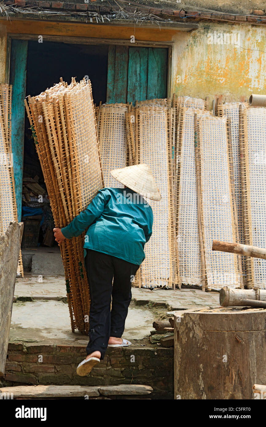 Woman in traditional Vietnamese cone hat carries racks of drying rice paper (used in cooking) in Tho Ha village - Stock Image
