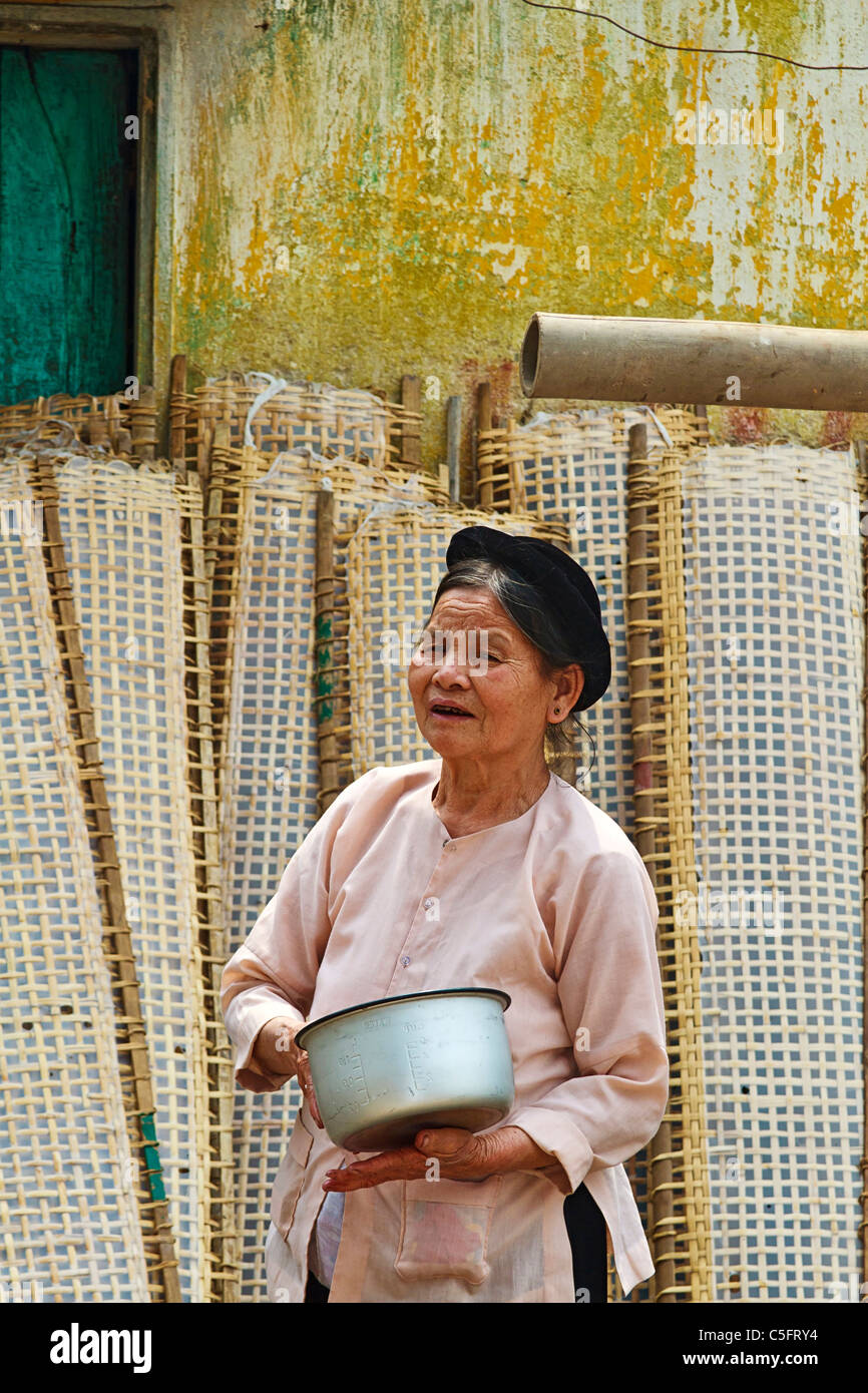 Elderly woman washes pot in front of racks of drying rice paper (used in cooking) in Tho Ha village near Hanoi - Stock Image