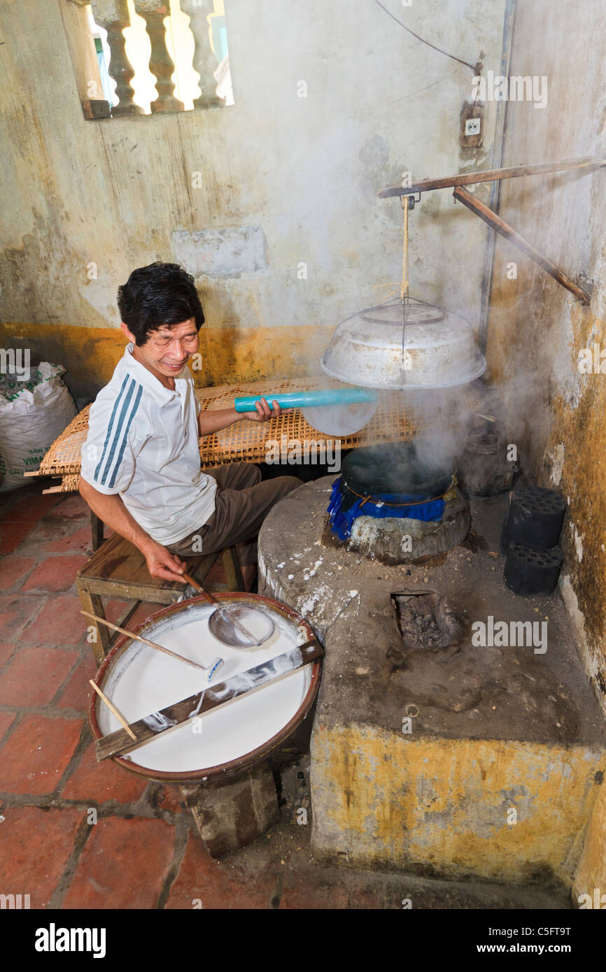 Viet Trinh Quang, 53, shows how he makes rice paper (for cooking) in the kitchen of his home, Tho Ha village, Vietnam - Stock Image