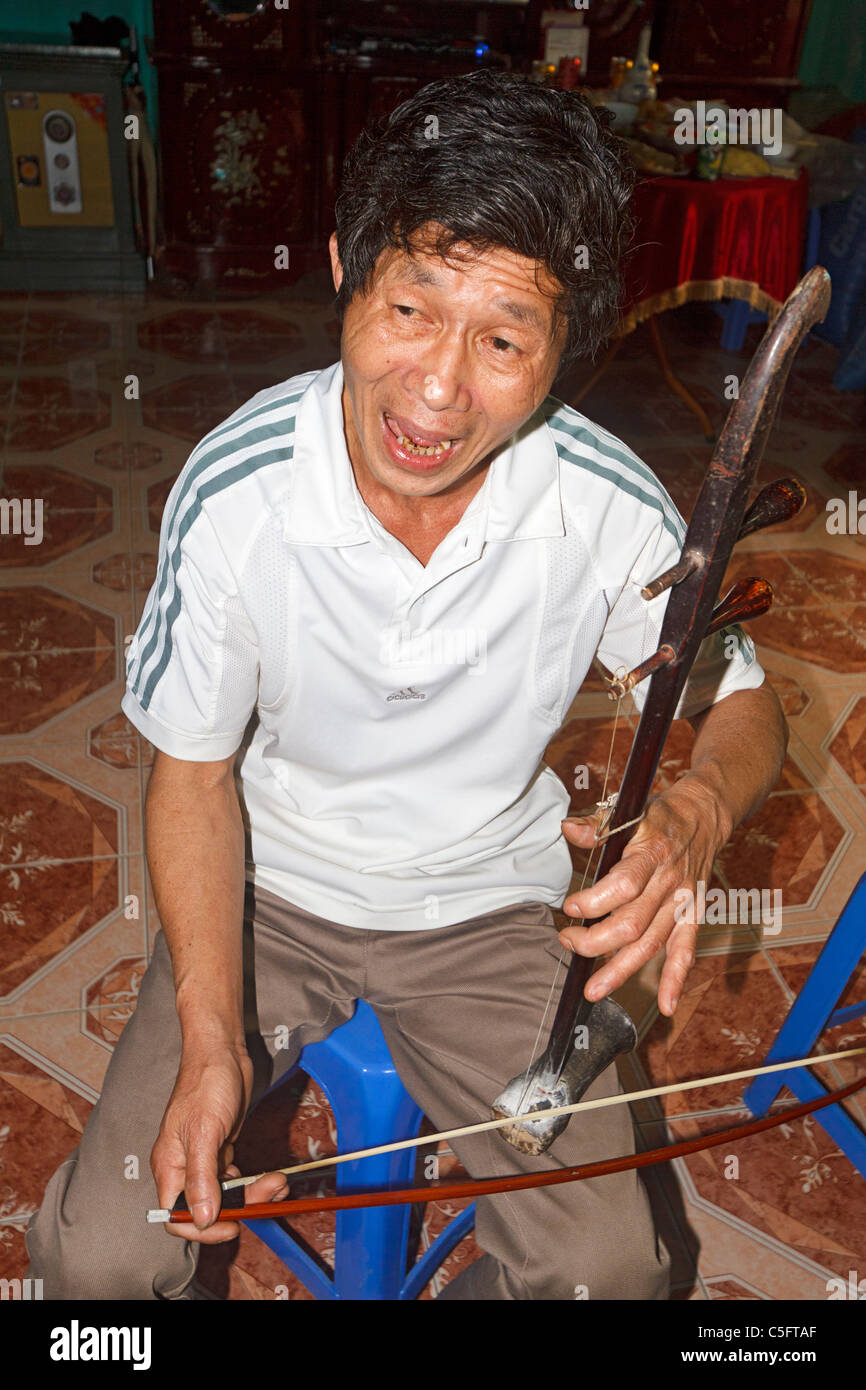 Viet Trinh Quang, 53, plays a stringed instrument known as a dan nhi in his home in Tho Ha village, Vietnam - Stock Image