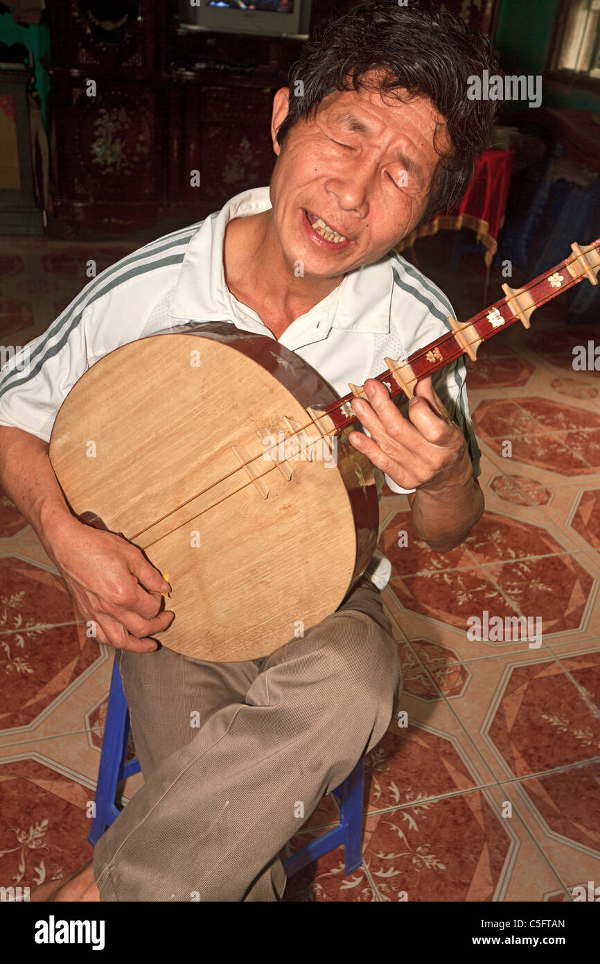 Viet Trinh Quang, 53, plays a stringed instrument known as a moon lute in his home in Tho Ha village, Vietnam - Stock Image