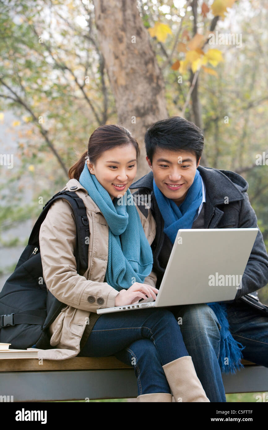 A young man and woman using a laptop together on a park bench - Stock Image