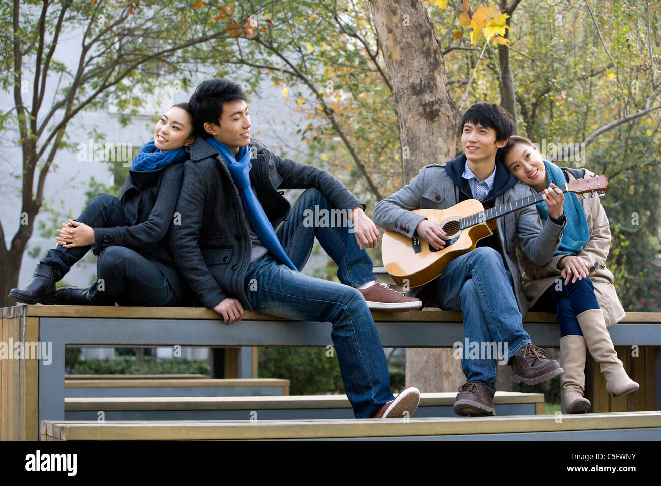 Two couples sit on a park bench and listen to a friend play guitar - Stock Image