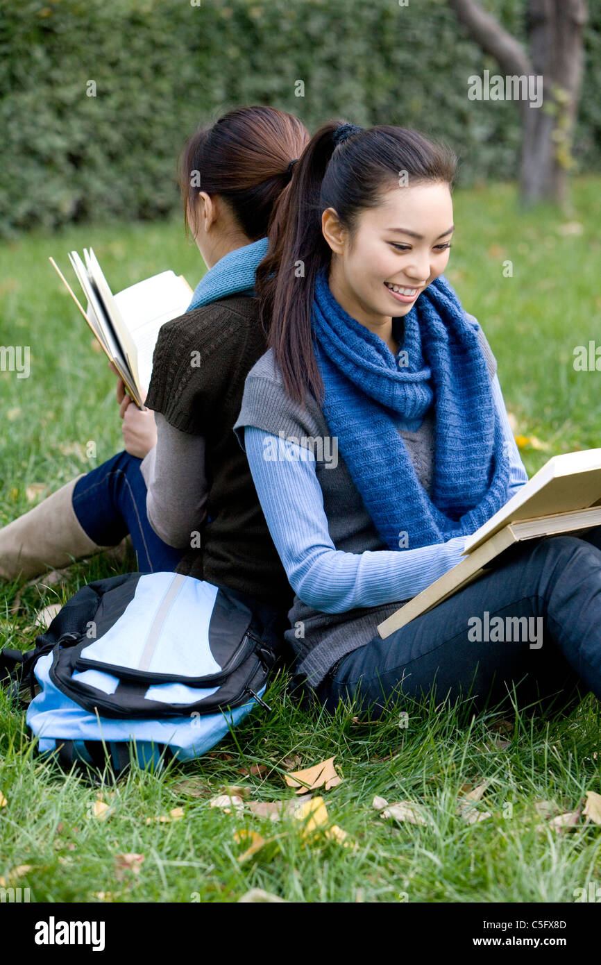 Two friends sitting back to back studying on a grassy area - Stock Image