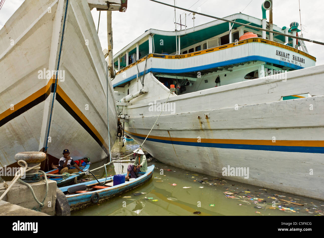 JAKARTA, INDONESIA - NOV 14 2010: Fisherman on boats resting amongst river pollution in Jakarta. - Stock Image
