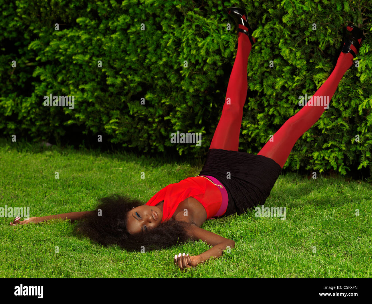 Young stylish black woman in fancy bright clothes lying on the grass in a park - Stock Image