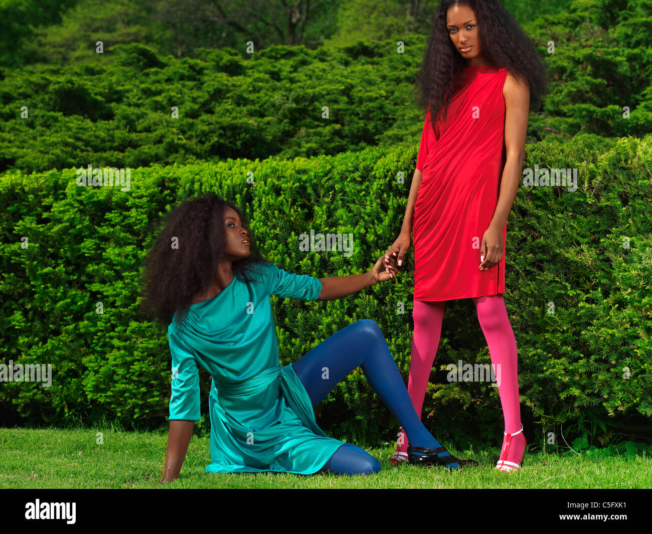 Two beautiful young women wearing bright colorful dressed in a green park Stock Photo