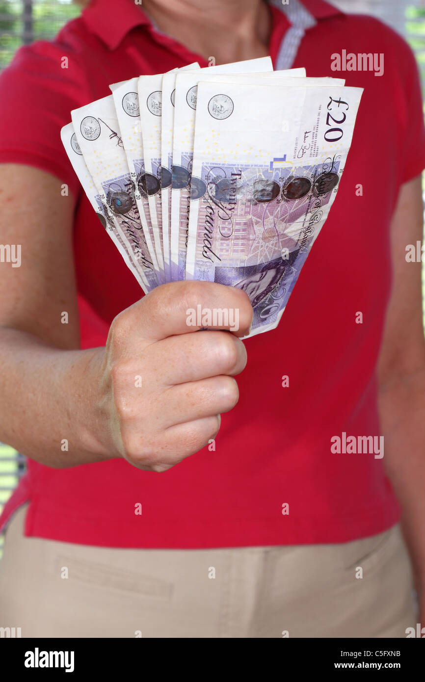 Woman Holding A Handful Of British 20 Pound Notes, Concept For Saving Money - Stock Image