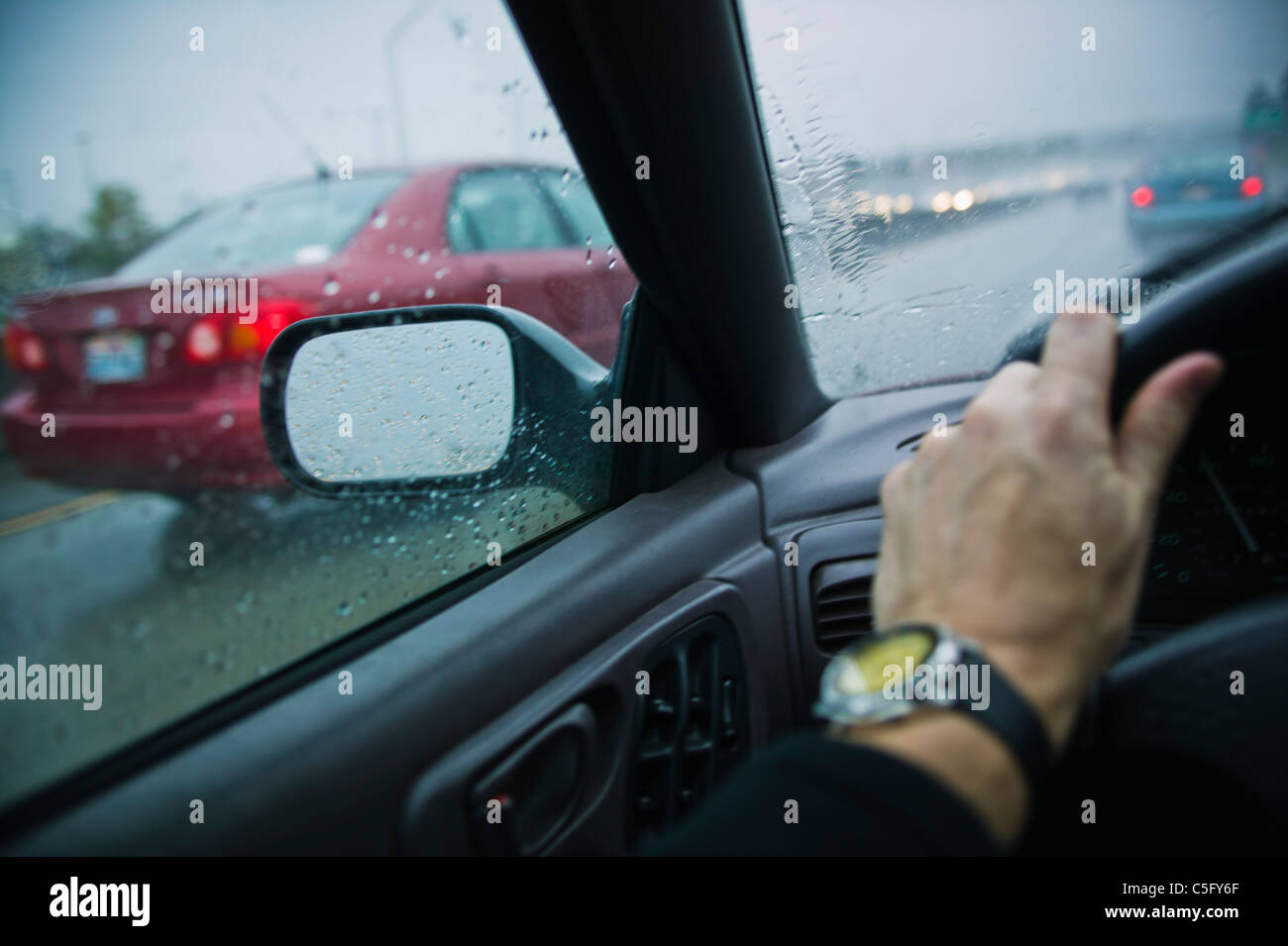 A first person point of view of driving on a freeway in the rain. - Stock Image