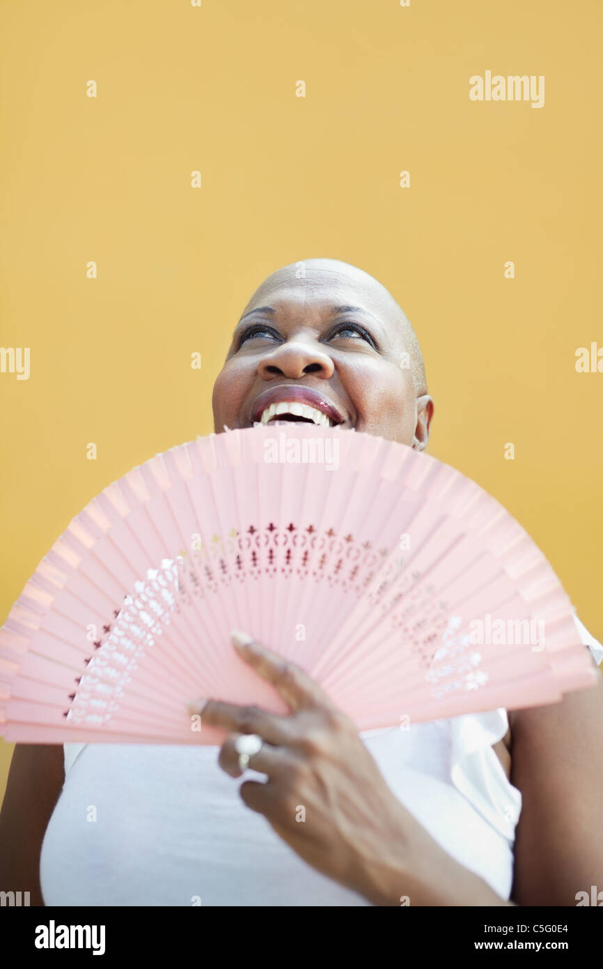 portrait of african 50 years old woman with bald head and fan smiling on yellow background. - Stock Image