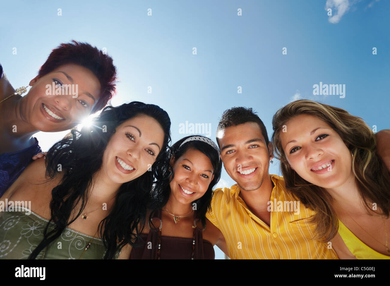 group of five young people looking at camera and smiling with sky in background. Low angle view, copy space - Stock Image