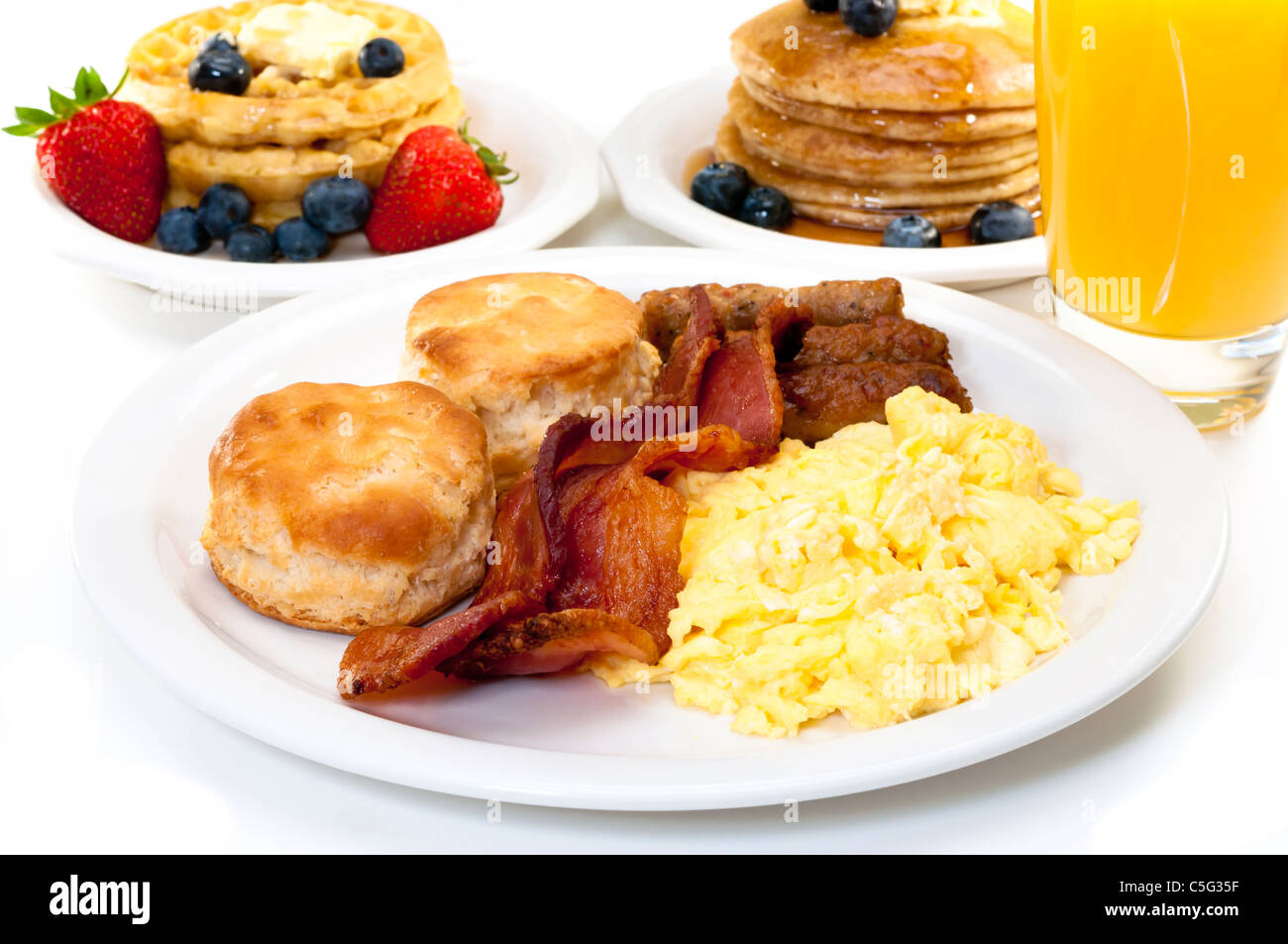 Breakfast plate with scrambled eggs, bacon, and buttermilk biscuits.  Waffles, pancakes, and orange juice in background. - Stock Image