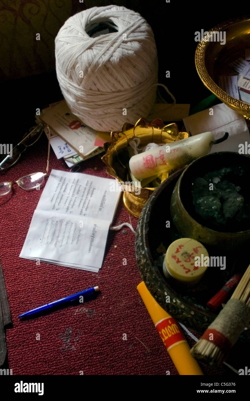 Reading glasses, a book and a ball of string are items among a monk's possessions at a Buddhist temple in Northern - Stock Image