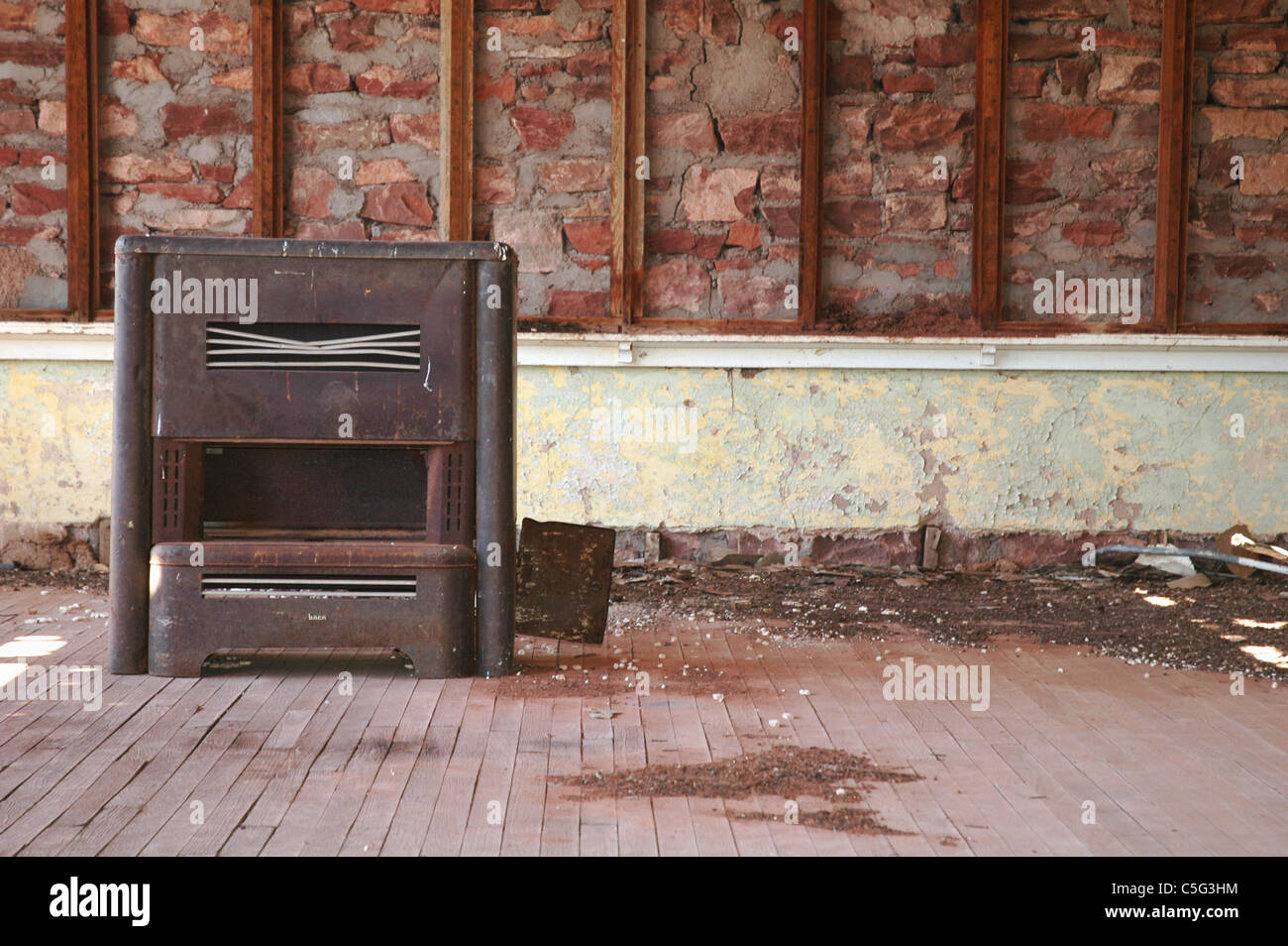 An old stove sits in front of a broken chalk board in a crumbling school house in the Cuervo New Mexico ghost town. - Stock Image