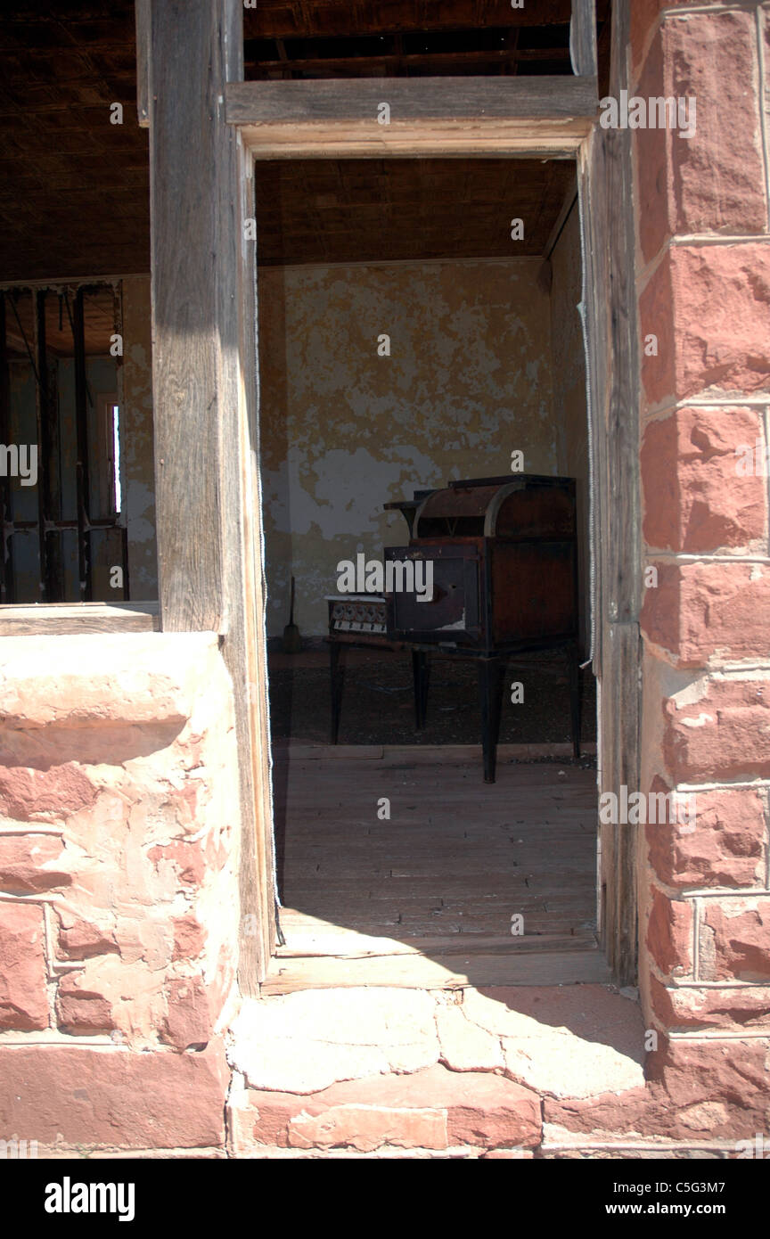An old stove can be seen through the doorway of the abandoned schoolhouse in Cuervo, New Mexico. - Stock Image