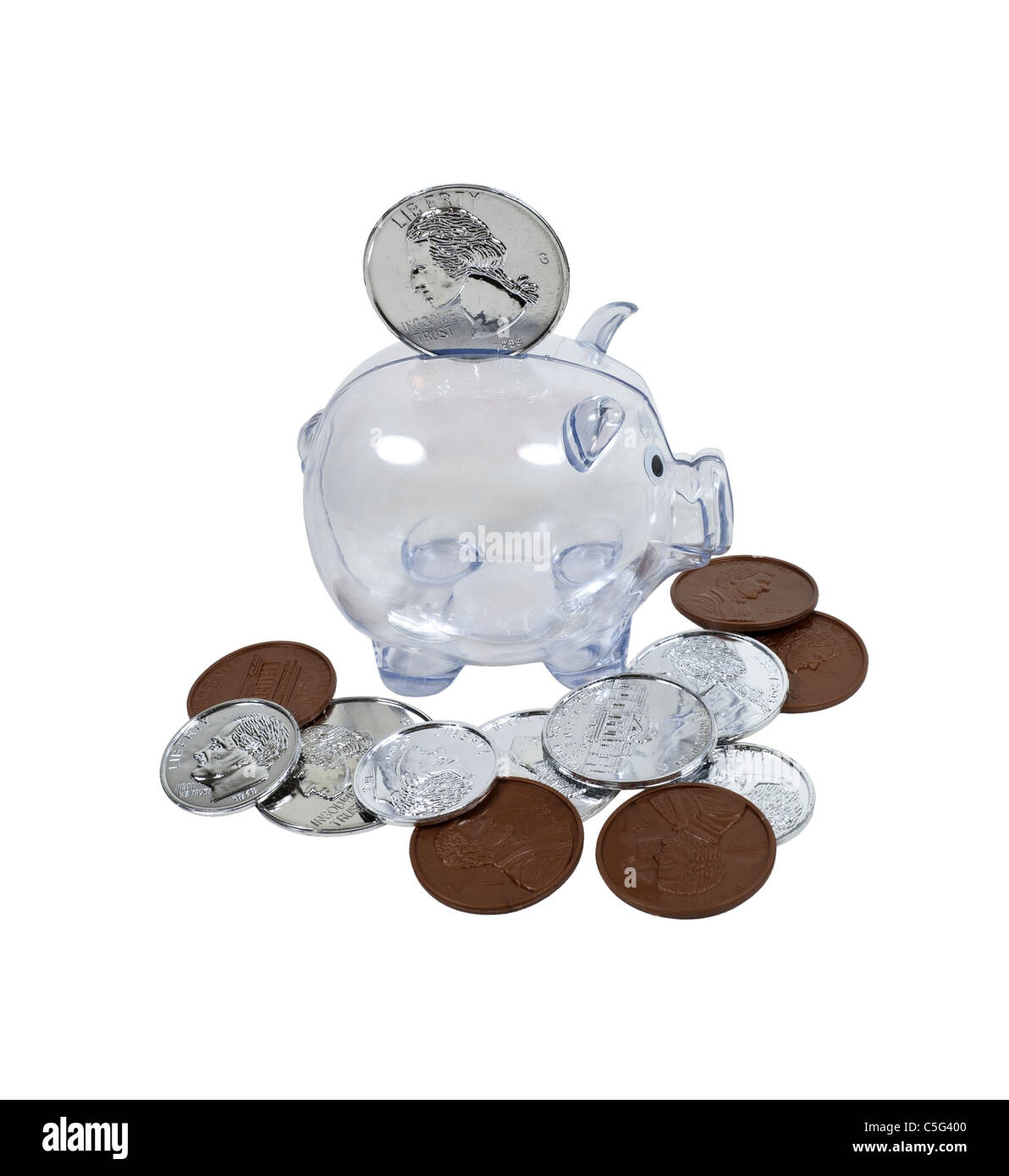Big savings shown by a clear piggy bank with large coins scattered around - path included - Stock Image