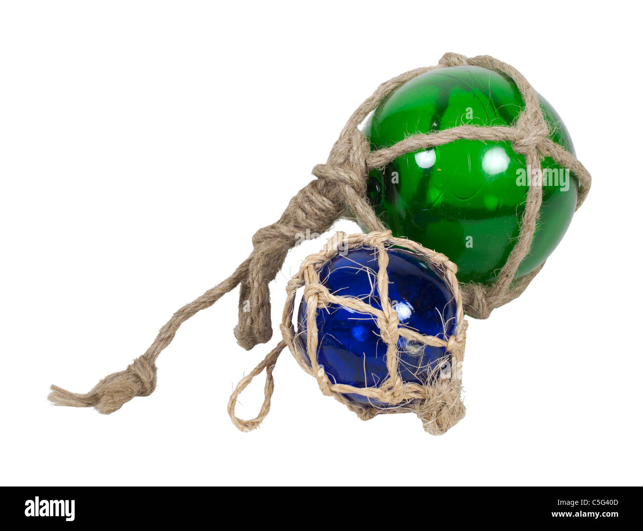 Green and blue nautical glass floats tied with rough rope - path included - Stock Image