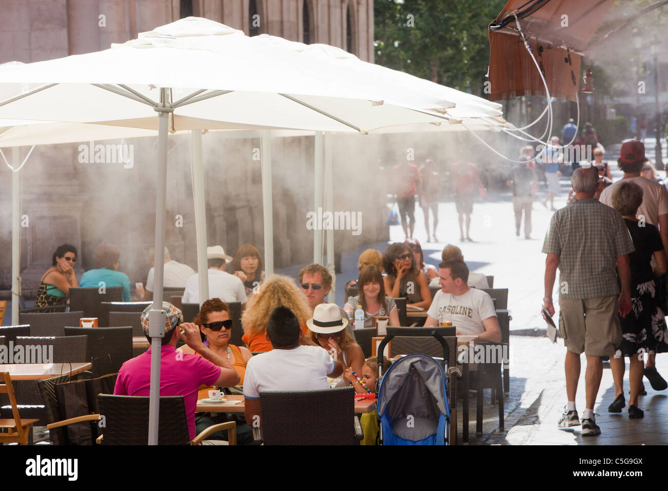 A cafe using cooling mist spray during a heat wave in Seville, Spain. Stock Photo