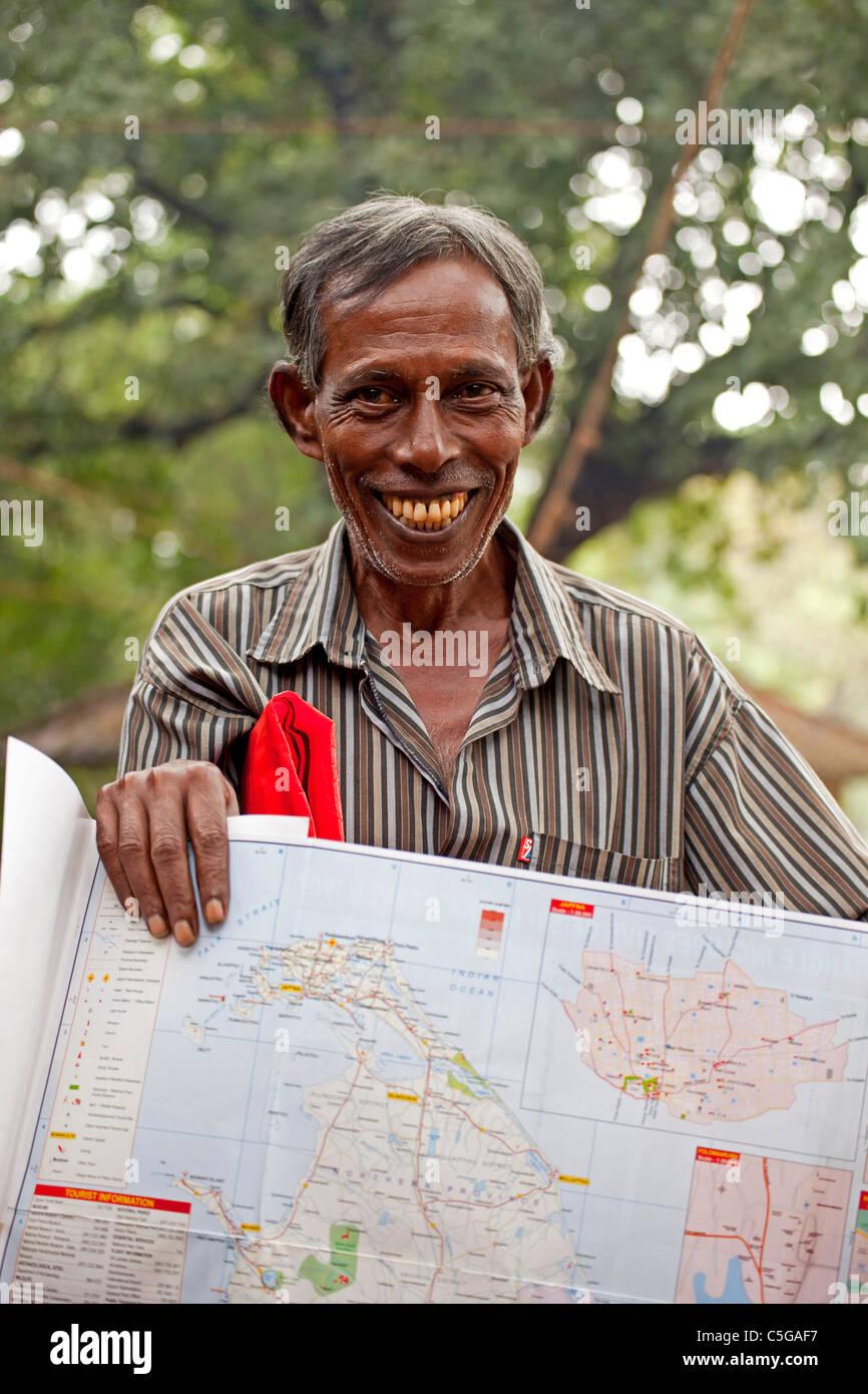 friendly salesman offering a map of Sri Lanka, Polonnaruwa, Sri Lanka, Asia - Stock Image
