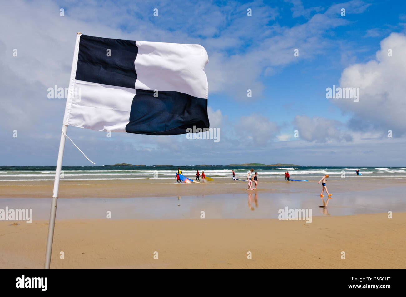Black and white chequered surfers flag warning swimmers that surfers and kayaks are in the area - Stock Image