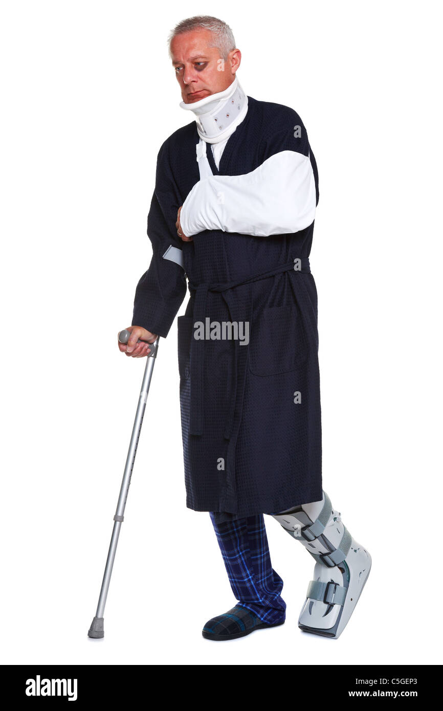Photo of a mature male with various injuries using a crutch, he's wearing a neck brace, arm sling and leg cast - Stock Image