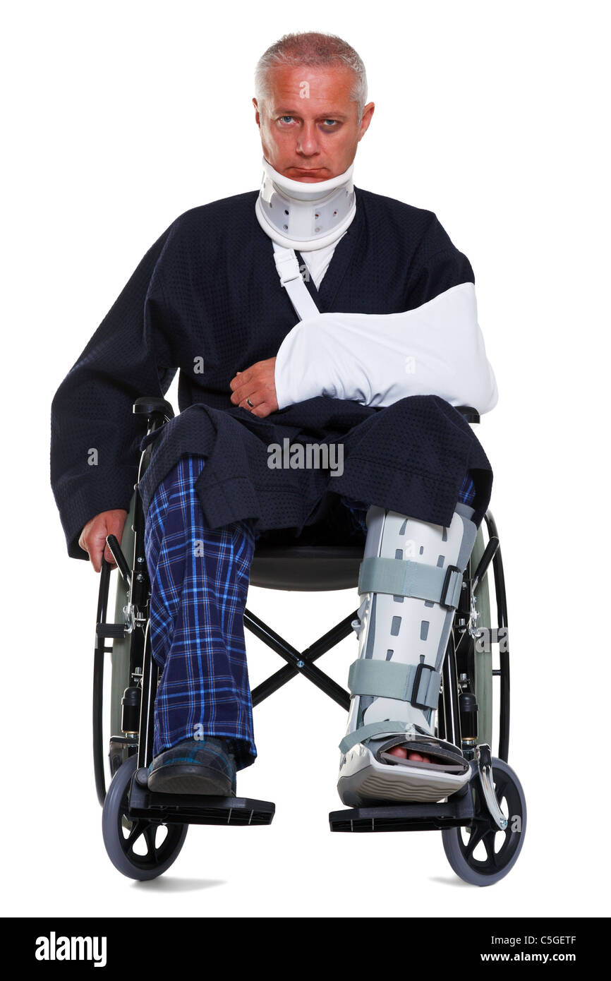 Photo of a mature male with various injuries in a wheelchair, he's wearing a neck brace, arm sling and leg cast - Stock Image