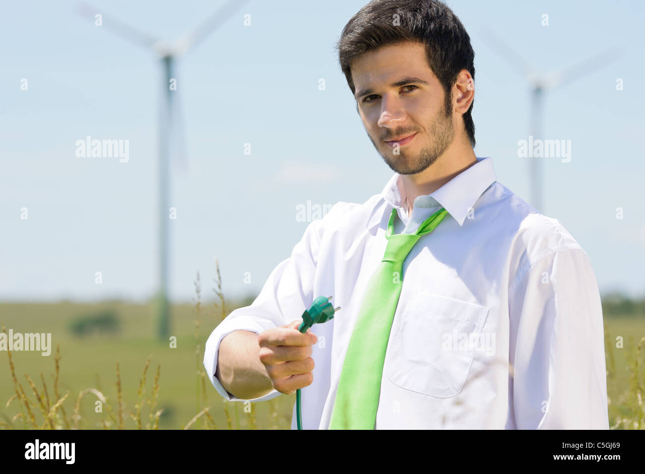 Green energy - young businessman hold plug in field with windmill - Stock Image