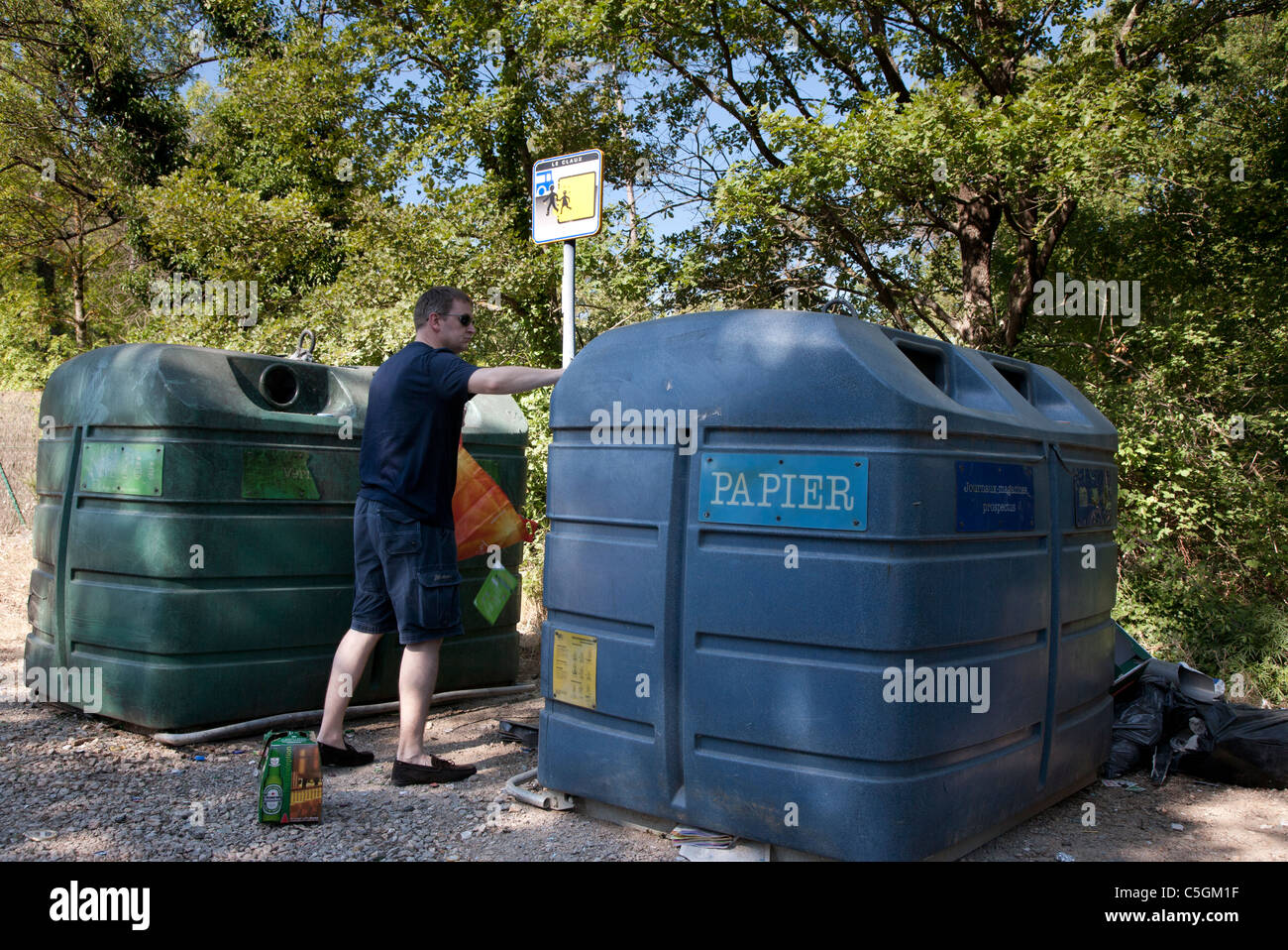 Man using recycle bins in Provence, France Stock Photo