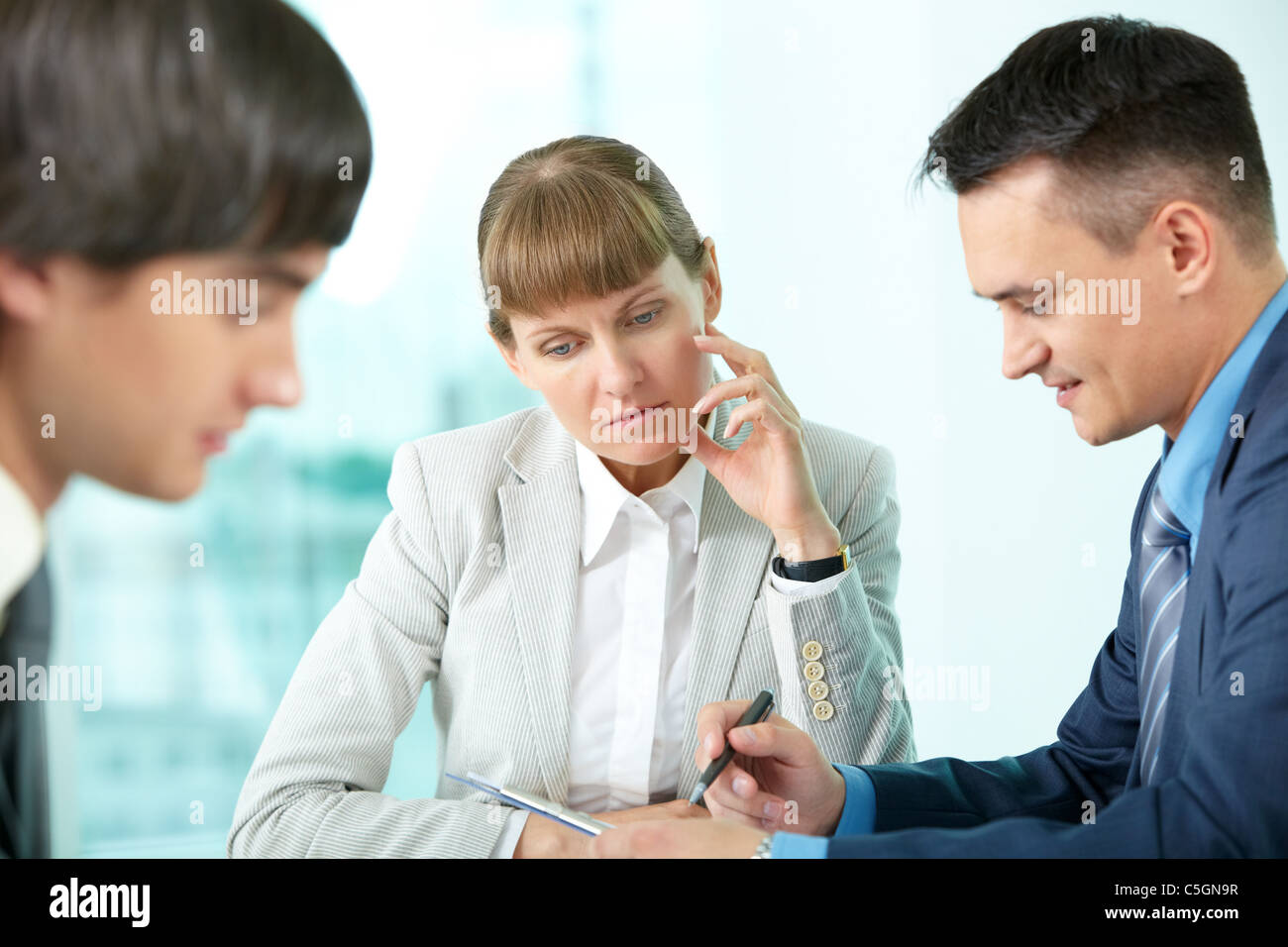 A businesswoman sitting in deep thought among her colleagues Stock Photo