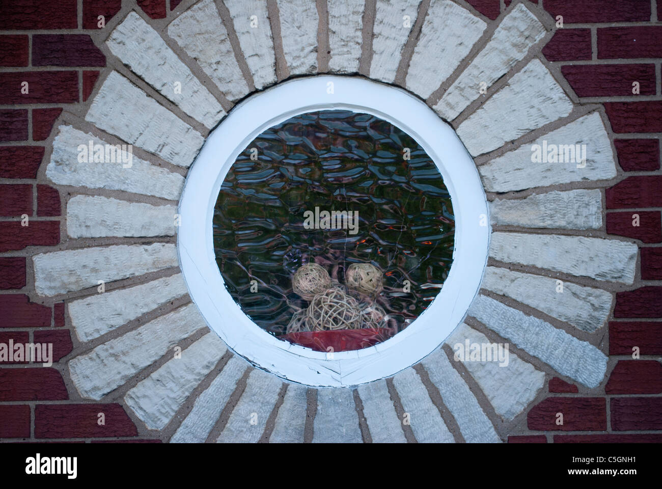 Round window with textured glass stone surround in red brick wall ...