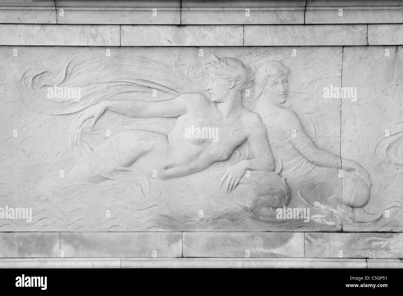 Languid sea nymphs ride stylised dolphins on the Victoria Memorial in London  - bass relief in white marble - Stock Image