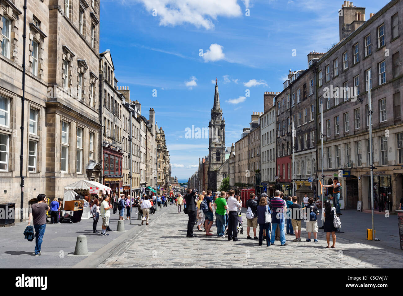 Shops and street entertainer on the High Street looking towards Holyrood, The Royal Mile, Edinburgh, Scotland, UK - Stock Image