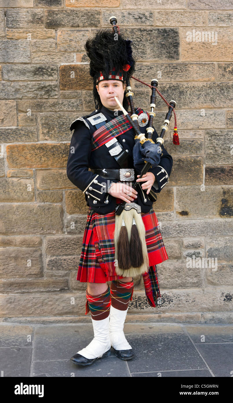 Scottish Piper in traditional dress playing the bagpipes outside Edinburgh Castle, Old Town, Edinburgh, Scotland, - Stock Image