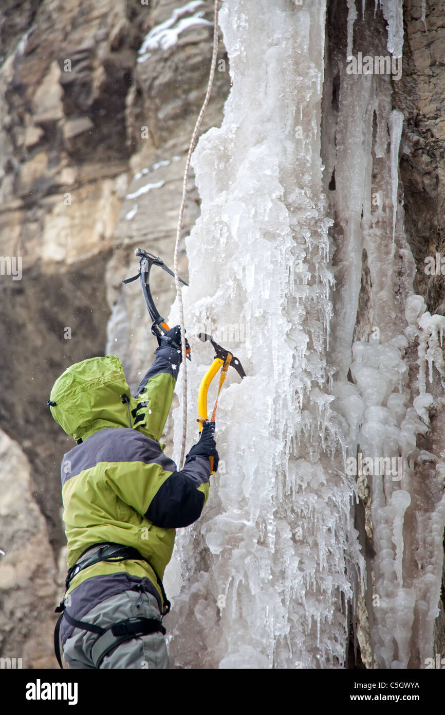 Man with ice axes climbing on icefall - Stock Image