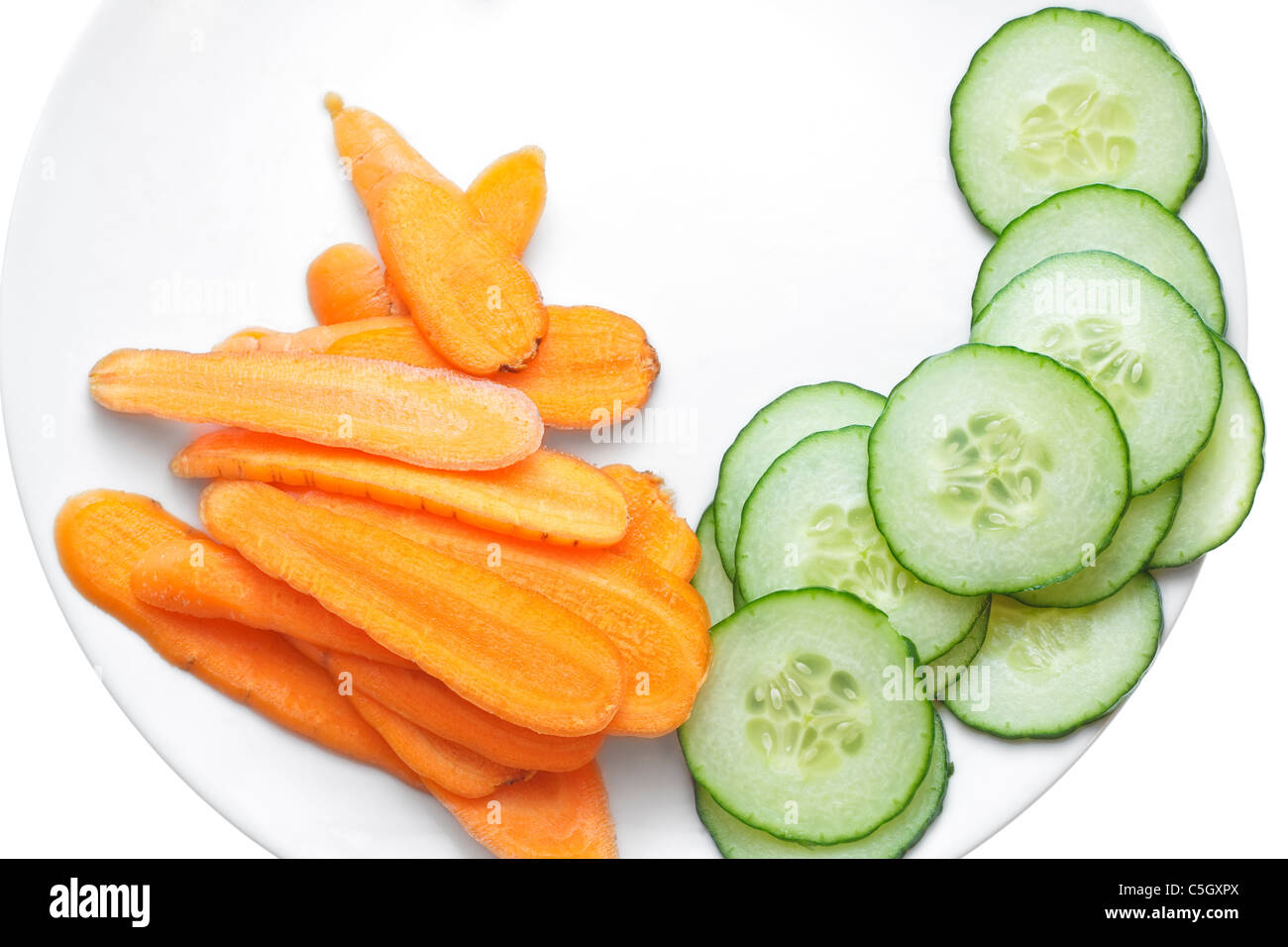 Fresh carrot and cucumber slices , arranged in a white plate. - Stock Image