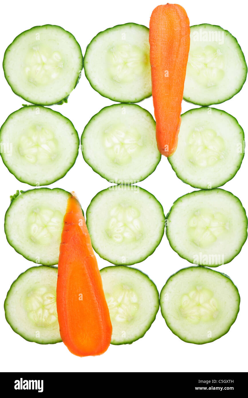 Pattern of fresh carrot and cucumber slices , isolated on a white background. - Stock Image