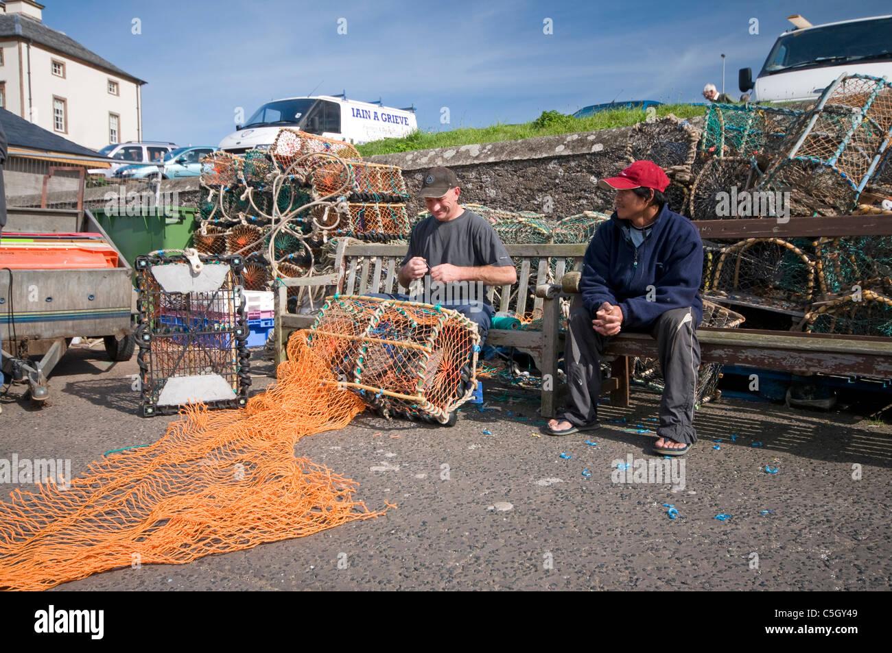 Fishermen mending nets on the harbourside at Eyemouth - Stock Image