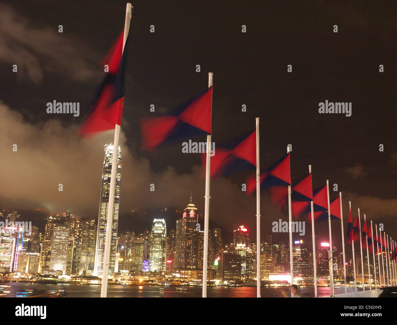 View looking up at a line of colourful flags flying in the wind with Hong Kong Island  in the background at night Stock Photo