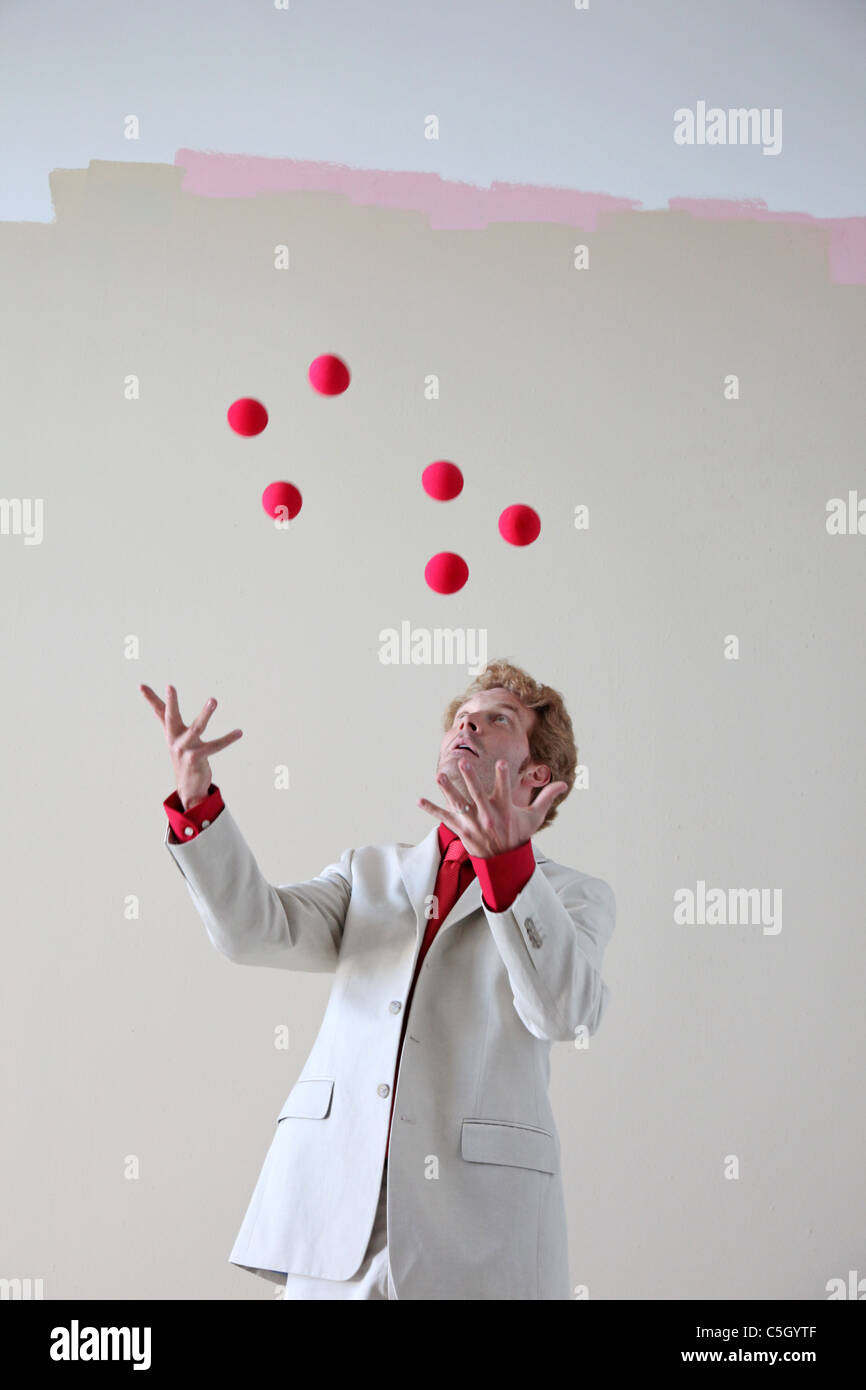 man juggles red balls in the air - Stock Image